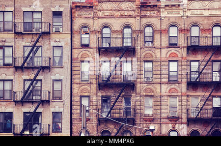 Old buildings with fire escapes, one of the New York City symbols, color toned picture, USA. - Stock Photo