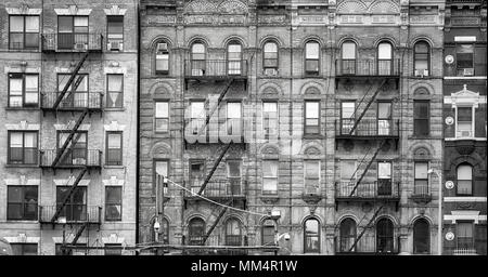 Black and white picture of old buildings with fire escapes, one of the New York City symbols, USA. - Stock Photo