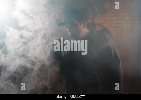 A cloud of vapor. Vaping man holding a mod. Brick background. Vape concept. Young man with beard vaping an electronic cigarette. Vaper hipster smoke v - Stock Photo