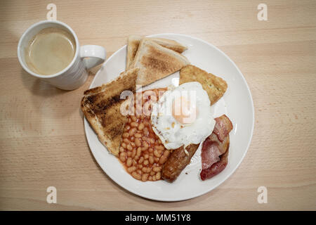 A full english breakfast with a black coffee on a cafe table - Stock Photo