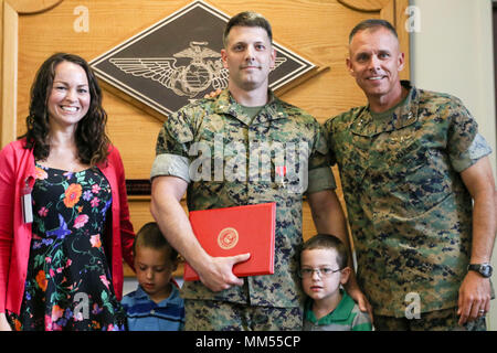 Maj. Adam McLaurin, center, poses with his family and Maj. Gen. Matthew Glavy after receiving a Bronze Star during an award ceremony at Marine Corps Air Station Cherry Point, N.C., Sept. 6, 2017. McLaurin received the medal for his meritorious service in connection with combat operations against the enemy while serving as the Officer in Charge, Provincial Augmentation Team, Special Operations Task Force West, Combined Joint Special Operations Task Force Afghanistan from October 2013 to August 2014. Glavy of the commanding general of 2nd Marine Aircraft Wing and McLaurin is a manpower officer a - Stock Photo