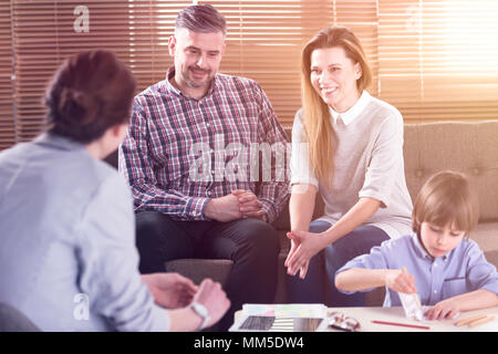 Happy family talking with their son's teacher in the office - Stock Photo