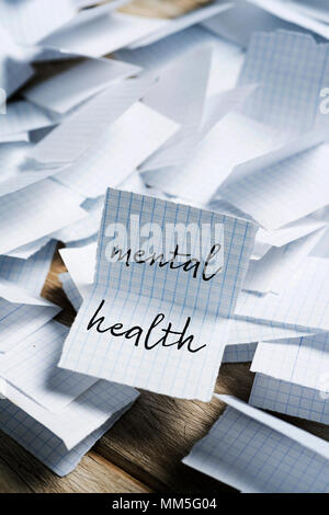 a pile of pieces of paper folded in half, and the text mental health in one of them unfolded in the foreground - Stock Photo