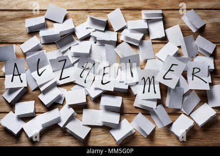 a pile of pieces of paper folded in half, and the text text alzheimer in some of them unfolded on top - Stock Photo