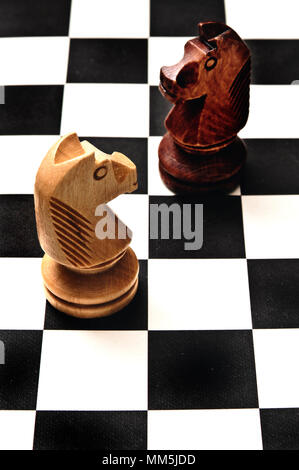 two chess knights on the chessboard, confronting each other. Challenge or decisions concept - Stock Photo