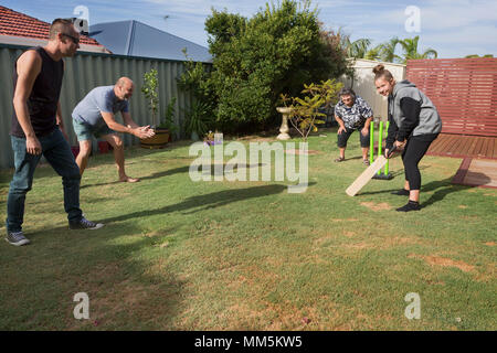 A family playing cricket in the back yard. - Stock Photo