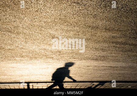 Defocused blurry shadow silhouette of a man walking on shiny road on sunset - Stock Photo