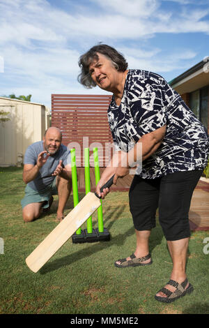 A Mother and Son pictured playing cricket in the back yard. - Stock Photo