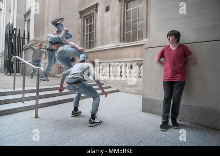 Free running parkour athlete jumping of stairs in public area, London, England - Stock Photo
