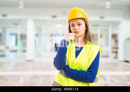 Young attractive female engineer thinking as pensive meditating for solution to problem concept on indoor lobby building background - Stock Photo