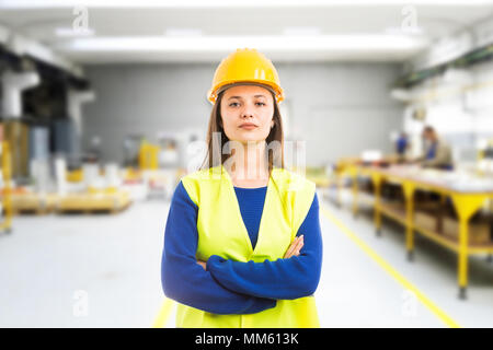 Proud confident young woman engineer with arms crossed as professional supervisor concept on indoor factory background - Stock Photo