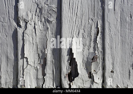 A closeup photo of an exterior of a wooden wall with some vertical lines and cracked old paint. - Stock Photo