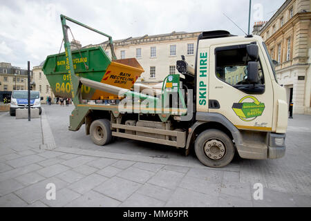 15b733319c ... recycling skip being delivered by lorry in the city centre of Bath  England UK - Stock