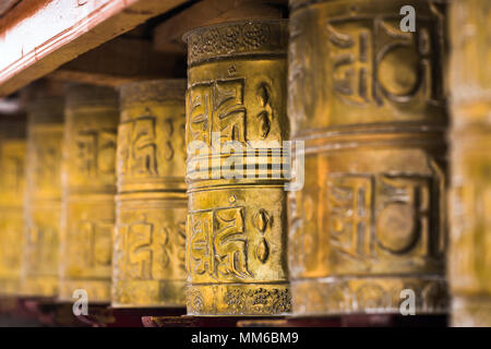 Tibetan buddhist praying wheels in Ladakh, India. Traditionally, the mantra Om Mani Padme Hum is written in Sanskrit on the outside of the wheel - Stock Photo