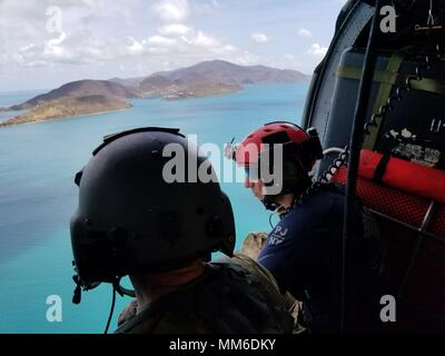 Aircrew survey the destruction from the helicopter over the U.S. Virgin Islands.    Airmen from the New York Air National Guard's 106th Rescue Wing fly over St. Thomas and St. John in an HH-60 Pave Hawk helicopter on 10 September, 2017.  They're searching for people in need of critical assistance in the wake of Hurricane Irma. - Stock Photo