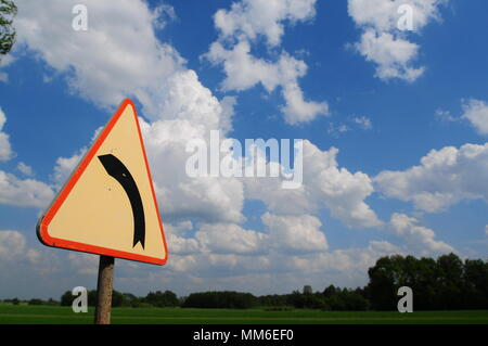 A road sign indicating a left bend in the road. with cloudy sky. - Stock Photo