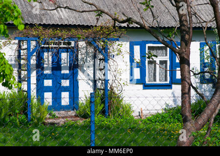 Small wooden house Painted on white and blue on Lubelskie region in Poland. Rural Architecture. - Stock Photo