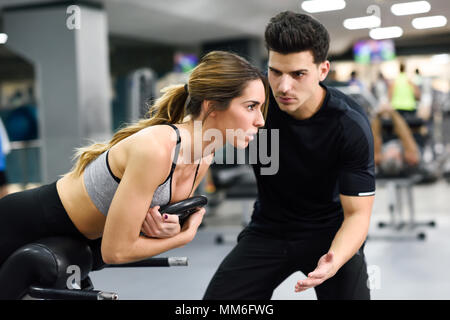 Personal trainer helping young woman lift weights while working out in a gym - Stock Photo
