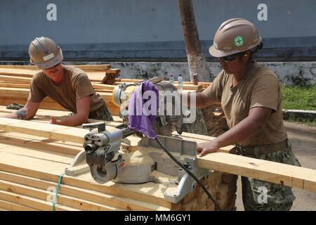170911-A-QE286-0114 PUERTO BARRIOS, Guatemala (Sept. 11, 2017) U.S. Navy Builder 3rd Class Herman Sebert, left, holds lumber in place while Builder Constructionman Rosa Gomez, both assigned to Naval Mobile Construction Battalion 1, makes cuts to build camp trashcans during Southern Partnership Station 17. SPS 17 is a U.S. Navy deployment, executed by U.S. Naval Forces Southern Command/U.S. 4th Fleet, focused on subject matter expert exchanges with partner nation militaries and security forces in Central and South America. (U.S. Army photo by Specialist Judge Jones) - Stock Photo
