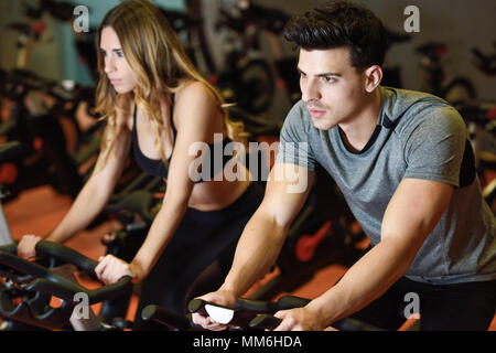 Young man and woman biking in the gym, exercising legs doing cardio workout cycling bikes. Two people in a spinning class wearing sportswear. - Stock Photo