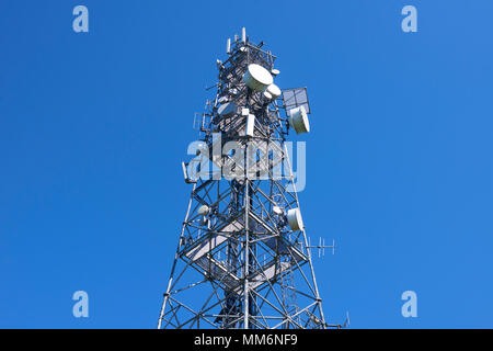 Telecommunication tower with antennas against the blue sky. View from below - Stock Photo
