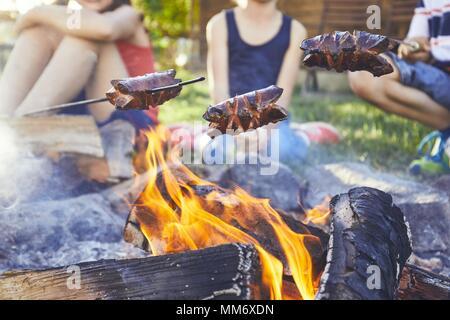 Children enjoy campfire. Girls (family) toasting sausages on the garden. - Stock Photo