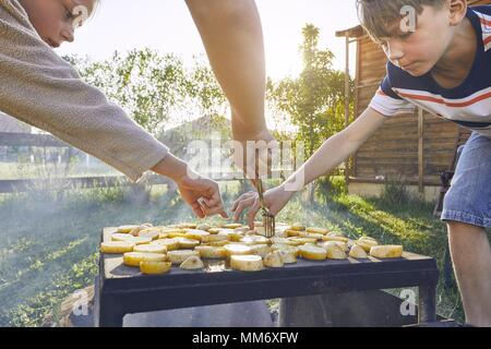 Children enjoy grilled. Siblings tasting potato from grill on the garden. - Stock Photo