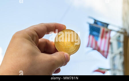 Holding a golden Bitcoin against flags of the United States and European Union, concept - Stock Photo