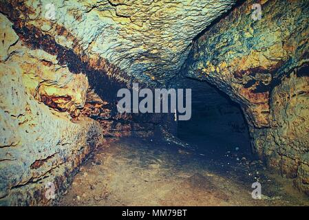 Bastion passage under city. Old catacombs built in orange sandstone rock.  The underground passages built by men for the defense during the war - Stock Photo