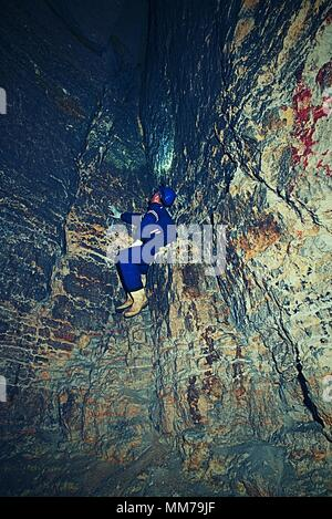 Man in dark old tunnel. Bastion passage under city  Stairs to the tunnel with walls made of orange sand stone. Staff in blue overall and safety helmet - Stock Photo