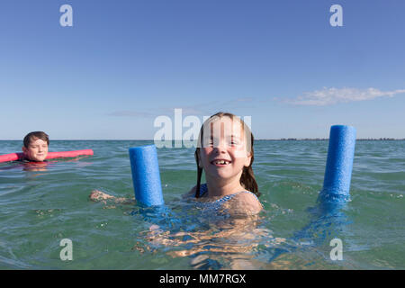 Two kids swimming, using flotation toys. - Stock Photo