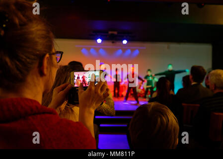 A woman filming a school concert with an iphone - Stock Photo
