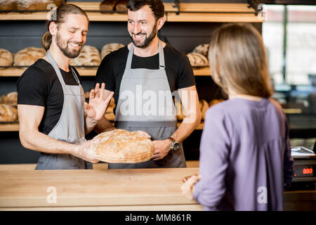 Woman buying bread in the bakery shop with man sellers - Stock Photo