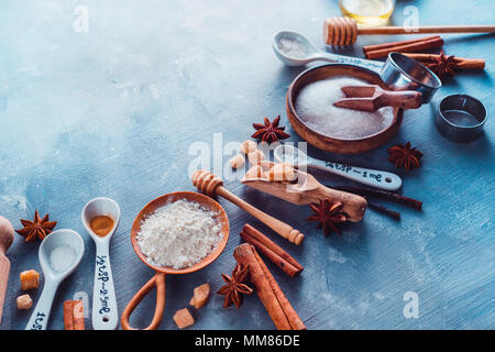 Cooking pastry close-up. Kitchen utensils for baking, flour, sugar, whisks, cookie cutters and a rolling pin a blue table with copy space. - Stock Photo