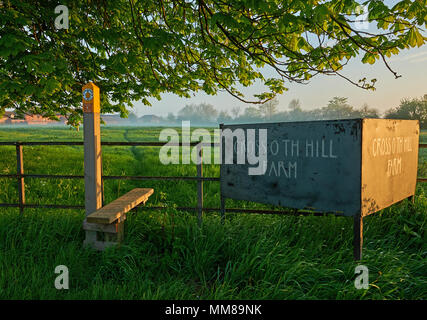 Public footpath and stile over a metal fence with a farm sign in rural Engalnd - Stock Photo