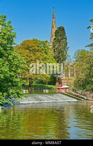 Stratford upon Avon Warwickshire and the River Avon weir with Holy Trinity church spire in the background - Stock Photo