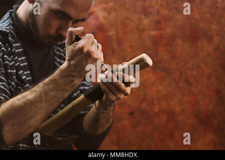 Man working in carpentry workshop. He pierces leather winding on wooden handle of ax. Men at work. Hand work. - Stock Photo