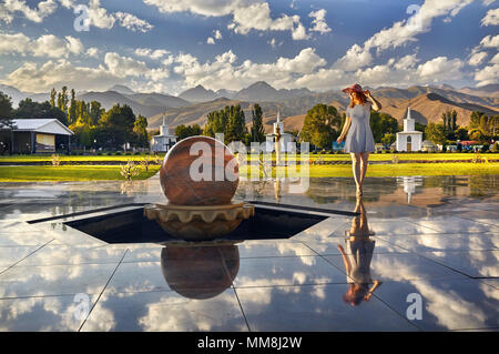 Tourist woman in red Hat and striped dress walking down the hall with stone sphere in Ruh Ordo cultural complex at Issyk Kul lake with mountains backg - Stock Photo