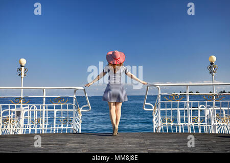 Tourist woman in red Hat and striped dress on the pier in Ruh Ordo cultural complex at Issyk Kul lake in Cholpon Ata, Kyrgyzstan - Stock Photo