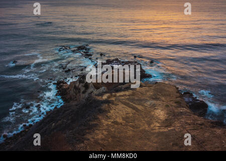 Long-exposure shot looking down a steep hiking trail at smooth waves crashing into Flat Rock Point rock formations after sunset, Palos Verdes Estates, - Stock Photo