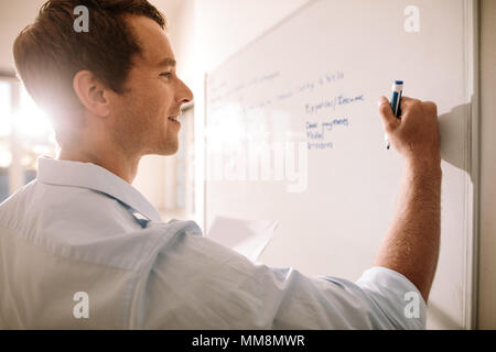 Entrepreneur making notes on a board. Close up of man writing on board. - Stock Photo