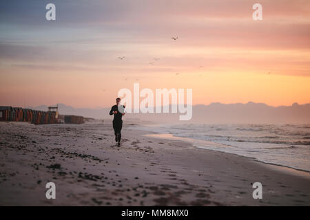 Full length shot of fit male runner running on the beach in morning. Fitness man jogging on the sea shore. - Stock Photo