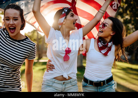 Three young female friends with American flag having fun in the park. Smiling group of women celebrating 4th of july outdoors. - Stock Photo