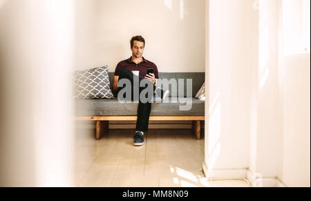 Businessman looking at mobile phone sitting at home with a coffee cup in hand. Entrepreneur operating mobile phone while relaxing at home. - Stock Photo