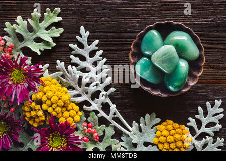 Green Aventurine Stones with Dusty Miller, Clustered Everlasting and Chrysanthemums on Dark Table with Space for Copy - Stock Photo