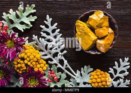Yellow Jasper Stones with Dusty Miller, Clustered Everlasting and Chrysanthemums on Dark Table with Space for Copy - Stock Photo