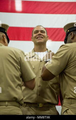 170915-N-BR087-137   PACIFIC OCEAN (Sept. 15, 2017) Chief Mass Communication Specialist Matthew White, from Kettering, Ohio, is frocked to chief petty officer during a CPO pinning ceremony in the hangar bay aboard USS John C. Stennis (CVN 74). John C. Stennis is underway conducting carrier qualifications and training for future operations after completing flight deck certification. (U.S. Navy photo by Mass Communication Specialist 3rd Class Cole C. Pielop/Released) - Stock Photo
