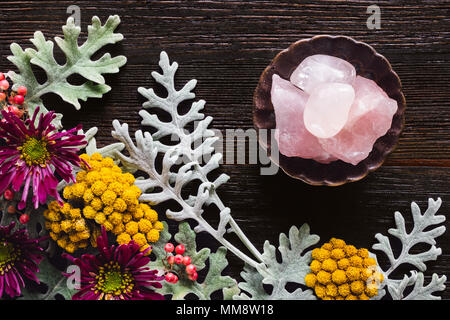 Rose Quartz Crystals with Dusty Miller, Clustered Everlasting and Chrysanthemums on Dark Table with Space for Copy - Stock Photo