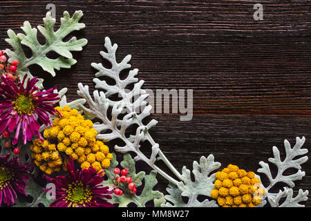 Floral Arrangement with Dusty Miller, Clustered Everlasting and Chrysanthemums on Dark Table with Space for Copy - Stock Photo