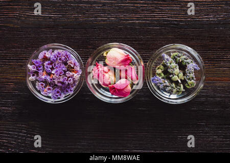 Bowls of Dried Lavender, Rose, and Sea Lavender Aligned and Centered on Dark Table with Space for Copy - Stock Photo